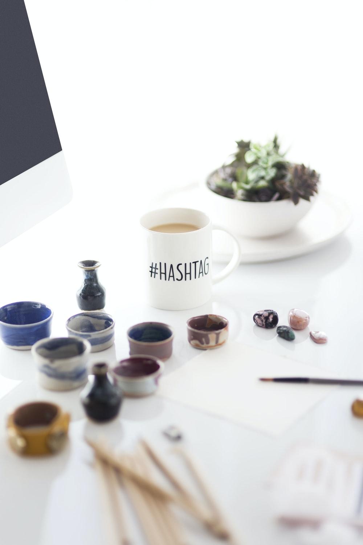 white #hashtag ceramic mug filled with coffee